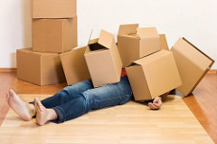photo of a person lying underneath boxes